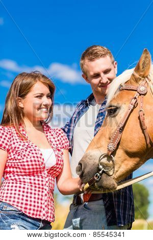 Couple petting horse on pony farm