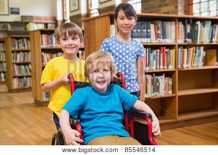 Cute pupils smiling at camera at the library at elementary school