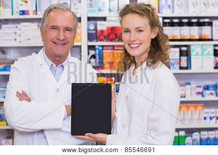 Pharmacist showing tablet pc at hospital pharmacy