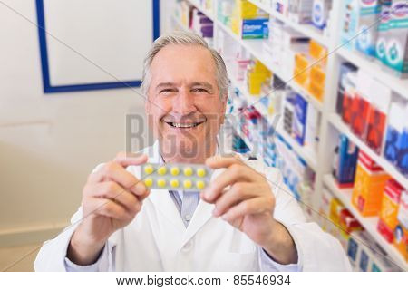 Senior pharmacist holding up blister packs at hospital pharmacy