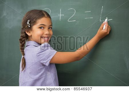 Pupil writing numbers on a blackboard at elementary school