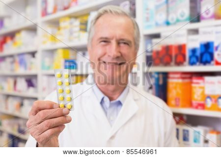 Senior pharmacist holding blister packs at hospital pharmacy