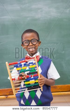 Smiling pupil holding abacus at elementary school