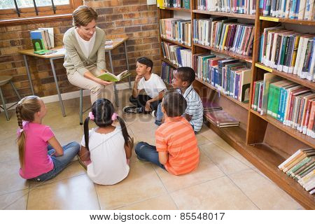Cute pupils and teacher having class in library at the elementary school
