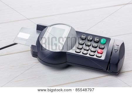 Credit card in banking machine on a wooden table