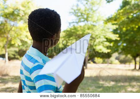 Cute little boy with paper airplane on a sunny day