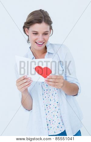 Smiling woman reading love letter on white background