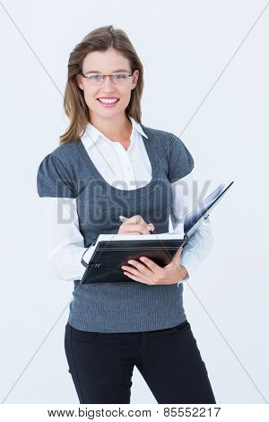 Happy woman writing in diary on white background