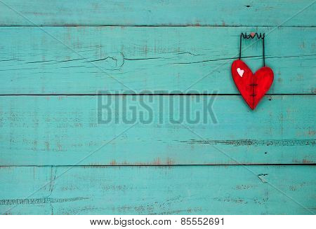 Red wooden heart hanging on turquoise background