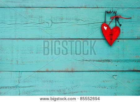 Red wooden heart with key hanging on turquoise painted wall