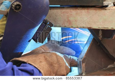 welder is welding steel structure with all safety equipment