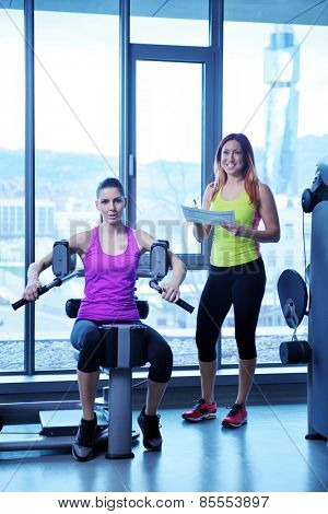Gym woman exercising with her personal trainer
