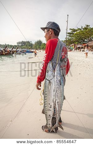 Local fisherman with two big fishes on the beach.
