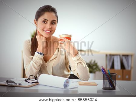 Beautiful  businesswoman enjoying coffee in bright office, sitting