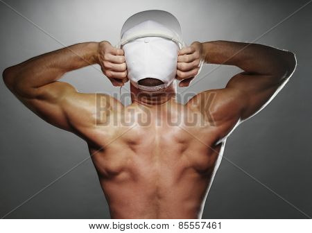 Close up Back View of a Shirtless Muscular Man with White Cap, Listening to Music Using Headphones, on a Gray Gradient Background.