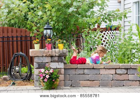 Cute Little Girl Playing On A Garden Wall