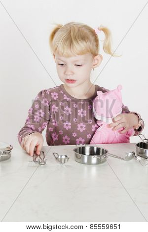 little girl playing with child dish and holding a doll