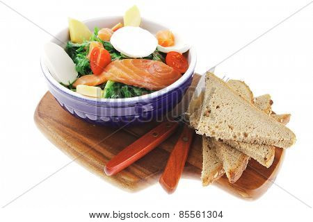 green salad with smoked salmon and bread on wood