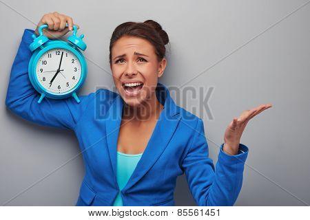 Awaken mixed race woman with alarm clock