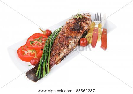 whole fried bass on plate, served with lemons and tomatoes isolated on white