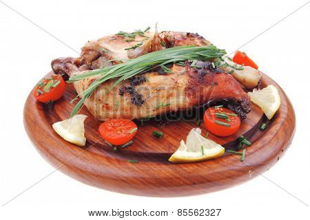 served grilled chicken legs with tomatoes lemon and chives on wooden plate isolated on white background