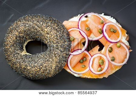Bagel with smoked salmon, cream cheese, capers and red onion.  Overhead view, on dark slate.