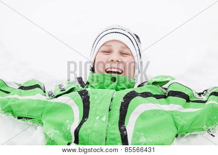 Young Boy In Winter Snow Laughing With Enjoyment
