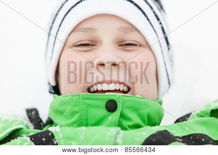 Happy Laughing Boy Lying In Winter Snow