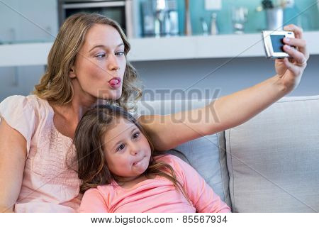 Happy mother and daughter taking selfie at home in the living room