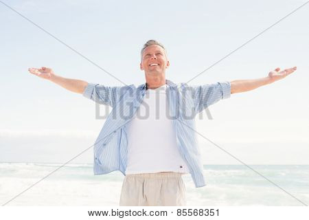 Handsome man with arms outstretched at the beach