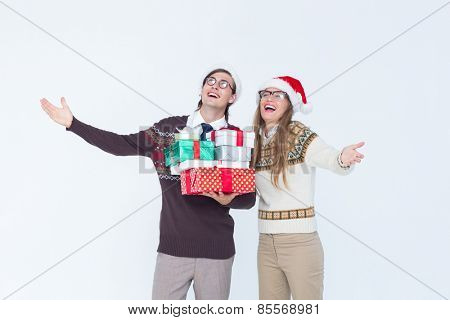 Geeky hipster couple holding presents on white background