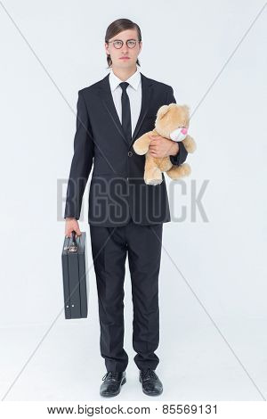 Geeky businessman holding briefcase and teddy on white background