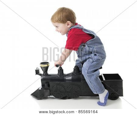 Side view of an adorable 2-year-old train engineer scooting along on a toy train engine.  On a white background.