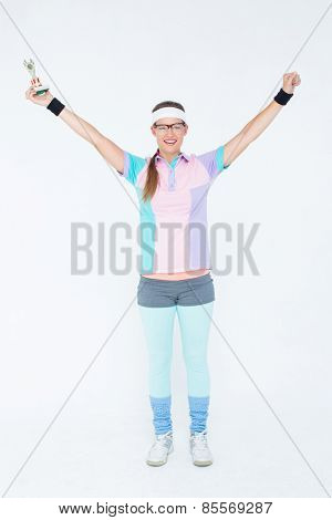Geeky hipster holding winners trophy on white background