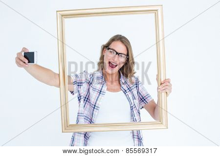 Pretty geeky hipster taking selfie with smartphone on white background