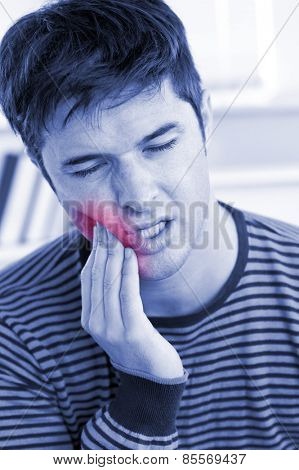 Portrait of a man having a raging toothache sitting in the livingroom at home