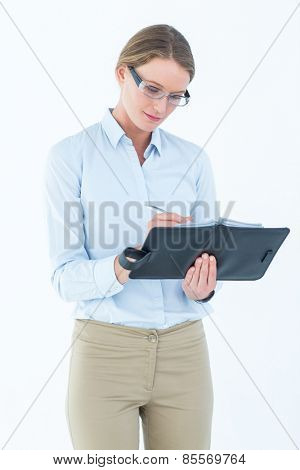Businesswoman writing in her diary on white background