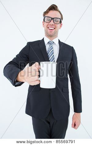 Happy geeky businessman holding coffee mug on white background