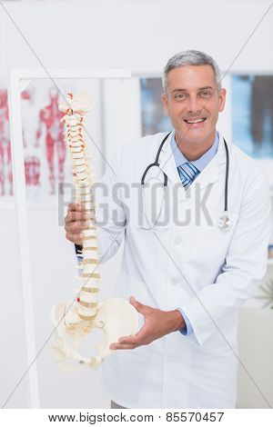 Happy doctor showing anatomical spine in clinic