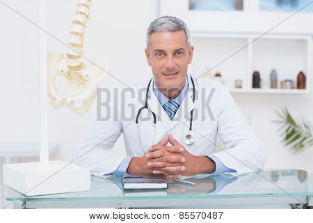 Doctor sitting at his desk smiling at camera in medical office