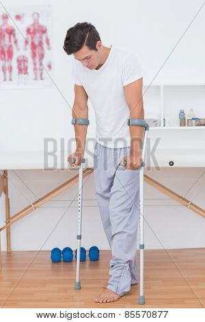 Patient walking with crutch in medical office