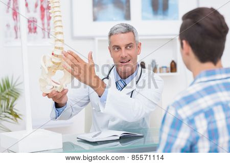 Doctor showing his patient a spine model in medical office