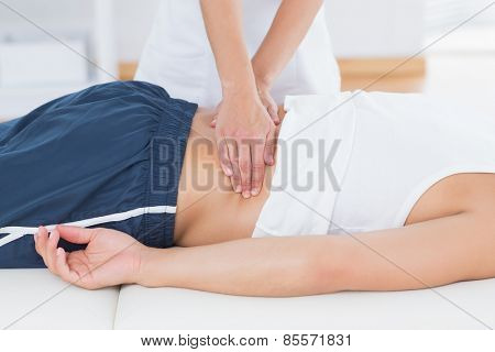 Physiotherapist doing back massage in medical office