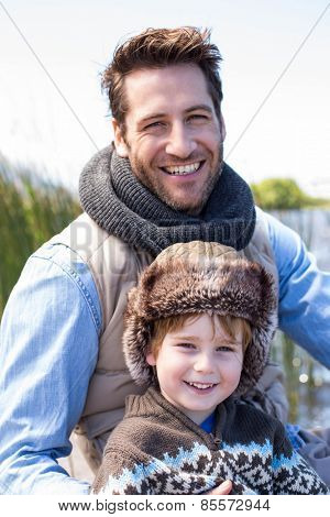 Happy casual father and son at a lake in the countryside