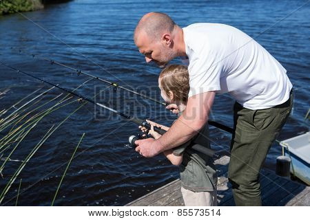 Happy man fishing with his son in the countryside