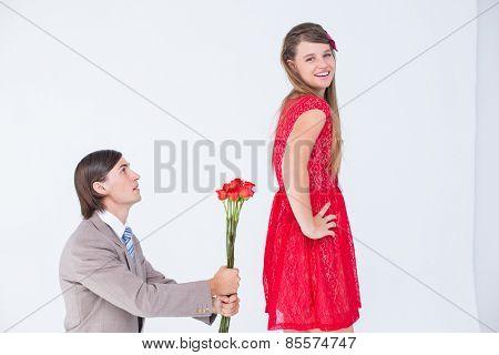 Hipster on bended knees behind his girlfriend on white background