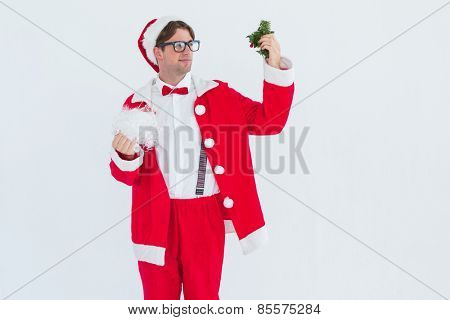 Geeky hipster in santa costume looking at mistletoe on white background