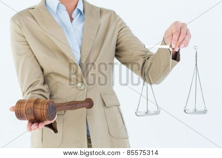 Young woman holding scales of justice and a gavel on white background