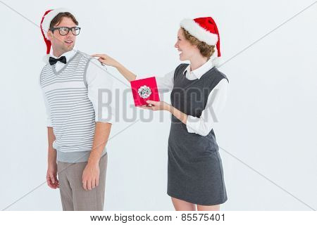 Geeky hipster offering present to her boyfriend on white background