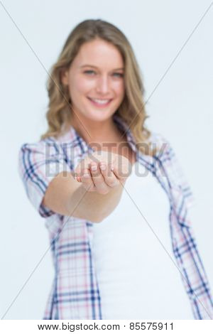 Pretty hipster presenting her hand on white background